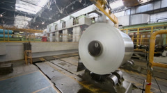 Worker oversees crane which moves roll of aluminum in workshop Stock Footage