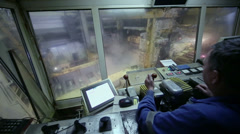 Man operates with control units of aluminum rolling process Stock Footage