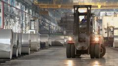 Man works on loader machine among rolls of aluminum in workshop Stock Footage