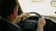Man turns steering wheel during drives car, view from behind Stock Footage