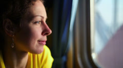 Flashes of sunlight on womans face which watches in window - stock footage