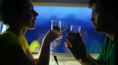 Couple drink tea and talk in dark compartment of train Stock Footage