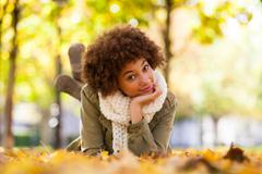 Autumn outdoor portrait of beautiful african american young woman lying down  Stock Photos