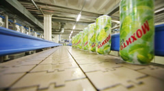 Wet green mojito cans aligned in single liner in factory - stock footage