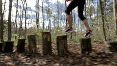 Woman running over stumps Stock Footage