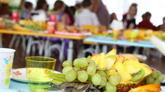 Composition of grapes, pineapple, apple and orange on children Stock Footage