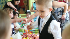 Children eat at the feast in kindergarten 1042 at party Stock Footage