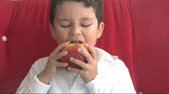 Child eating red apple Stock Footage