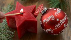 Christmas candle in star shape is lit with a match. Stock Footage