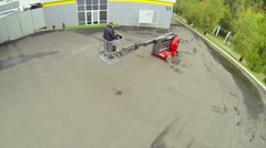 Worker maneuvering lift truck in courtyard Stock Footage