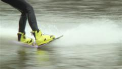 Riding wake-boarder towed cable jumps trampoline, water surface, click for HD Stock Footage