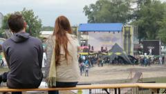 Young couple watching show sitting bench, rock concert contest, click for HD Stock Footage