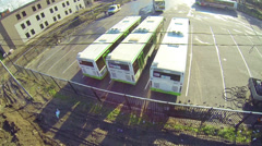 Several buses parked in large parking lot during the day Stock Footage
