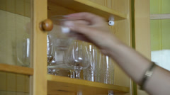 Closeup of hands put vintage crystal glasses to wall cabinet Stock Footage