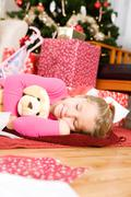 christmas: girl asleep after opening presents - stock photo