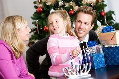 holidays: fun family time lighting menorah - stock photo