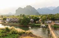 Stock Photo of view of wooden bridge over river song, vang vieng, laos.