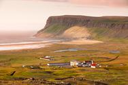 Stock Photo of icelandic landscape with small location at ocean coastline