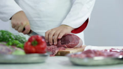 Low angle shot of butcher cutting cuts of red meat Stock Footage