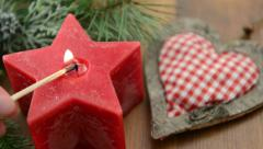 Christmas candle in star shape is lit Stock Footage
