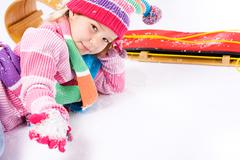 Stock Photo of winter: little sled girl with handful of snow