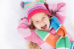 Stock Photo of winter: laughing little girl lying in snow