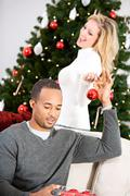christmas: man helping woman decorate christmas tree - stock photo