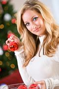 Christmas: holding a christmas ornament Stock Photos