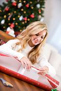 christmas: woman wrapping gift box - stock photo