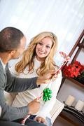 christmas: woman gives man golf club for christmas - stock photo