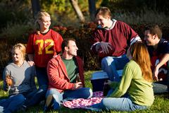 football: group of friends having picnic in park - stock photo