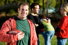 football: man stands with football and friends - stock photo