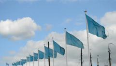 Blue flags line on blue sky with white clouds, Stock Footage