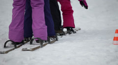 Shot of legs of kids trying to synchronize their walking on wooden skis - stock footage
