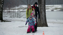 Family trying to walk on large skis when kid falls Stock Footage
