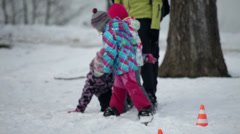 Kids smile and playfuly fall one after another when family walks on large skis - stock footage