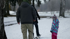 Two parents walk on the large skis one in the front one at the back - stock footage