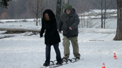 Two parents are walking on large skis without any hassle Stock Footage