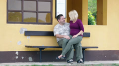 Pregnant woman sitting in boyfriend's lap while he is showing appreciation Stock Footage