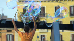 Spain Catalonia Barcelona street artist blowing soap bubble in the air Stock Footage