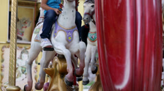 Close shot of wooden horses and carriges on spinning roundabout Stock Footage