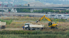 Excavator is loading big white truck with soil Stock Footage