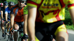 Close shot of large group of competing cycle racers on sunny day - stock footage