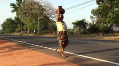 Local woman carries a crock on her head along the road. Sri Lanka. Stock Footage