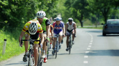 Group of competing cyclist is driving in straight line on sunny day Stock Footage