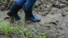 Woman legs with gumboots walk on wet dirt mud leaves footprints - stock footage