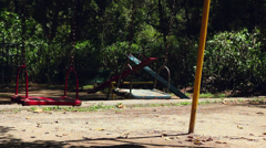 Empty swings swaying at playground - stock footage