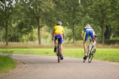 Two cyclists on the road in nature - stock photo