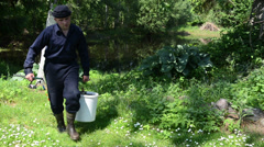 Weary man returns from the pond with bucket full of fish Stock Footage
