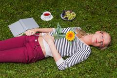 Blond girl lying in a meadow and dreams to himself Stock Photos